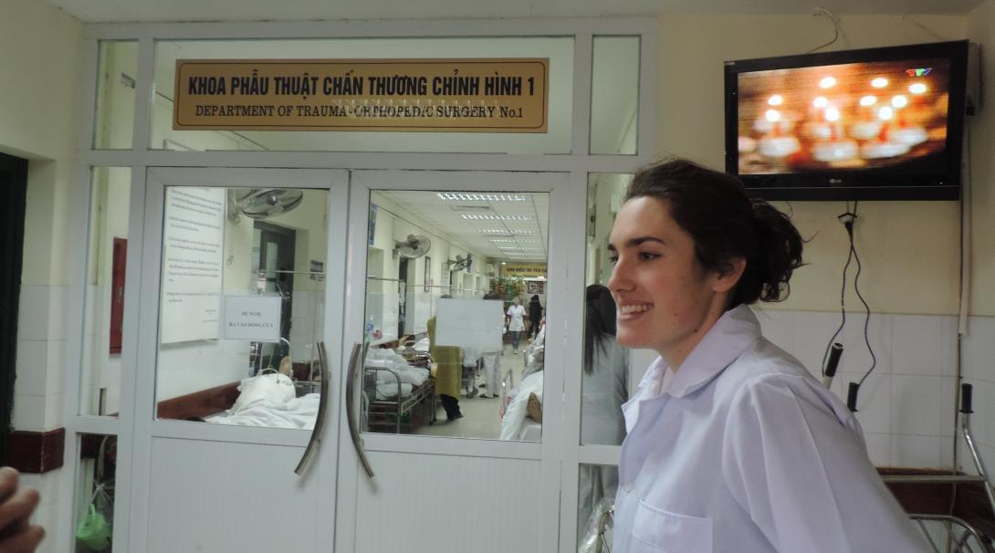 A female Projects Abroad intern is pictured smiling in a hospital room whils ton her nursing internship in Vietnam.